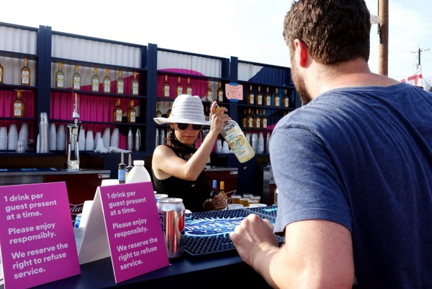 A female bartender serves free drinks at Spotify House South by Southwest, SXSW, 2016. Thousands of bands and music ...