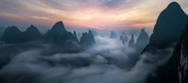 A view of the many karst mountains peaking through a river of fog. Taken on spring morning in Guangxi, China.