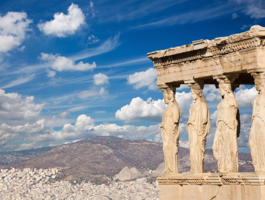 The Acropolis, Greece: The statues of Erechtheion on Acropolis and the town in morning light.