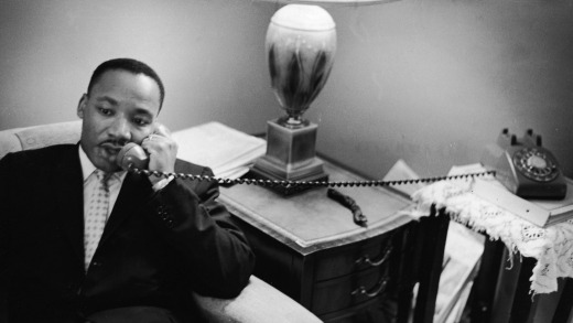American civil rights leader Dr. Martin Luther King, Jr. (1929 - 1968) sits on a couch and speaks on the telephone after ...