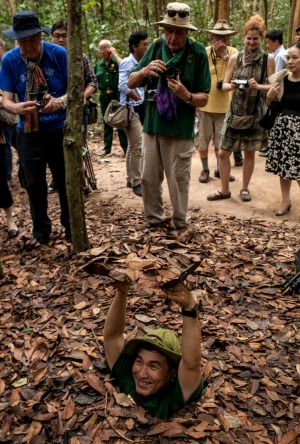 A Vietnamese tour guide demonstrates how to disappear into the Cu Chi tunnels through a camouflaged hole during a tour ...