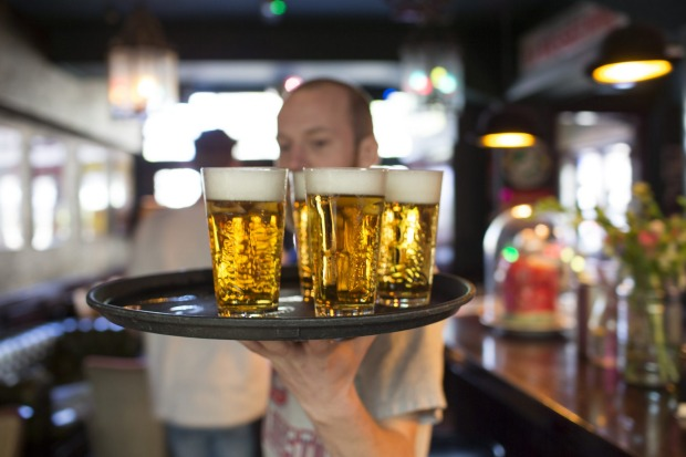 A barman carries a tray of draught Grolsch beer glasses, produced by SABMiller Plc, in a bar in Utrecht, Netherlands.