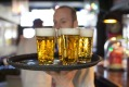 A barman carries a tray of draught Grolsch beer glasses, produced by SABMiller Plc, in a bar in Utrecht, Netherlands, on ...
