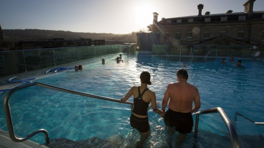 Bathers enjoy naturally warmed spa water as they relax in the rooftop pool of the Thermae Bath Spa, Britain's only ...