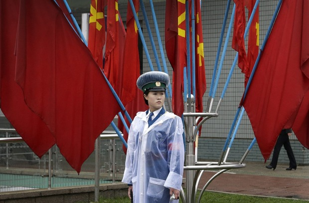A North Korean traffic police woman stands in front of Workers' Party flags decorating the streets in Pyongyang.