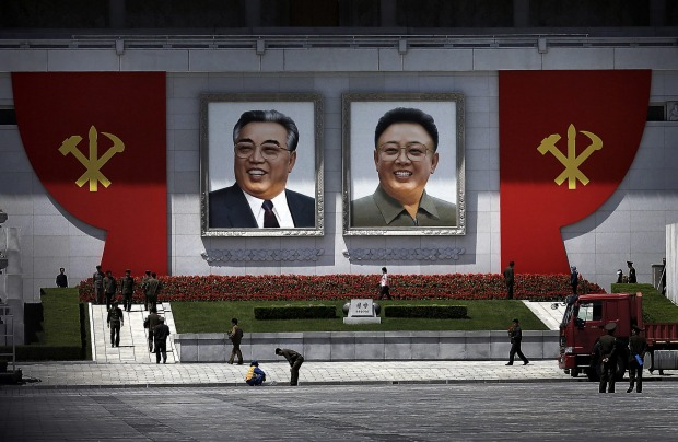 The ruling Workers' Party symbols are erected by the portraits of the late North Korean leaders Kim Il Sung, left, and ...