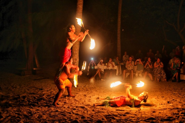Polynesian fire dancers perform for guests on a tiny uninhabited island in the lagoon of Bora Bora.