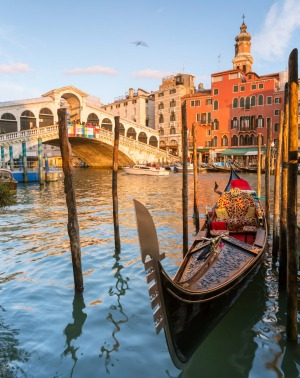 Gondola moored at sunset on the Grand Canal, at Rialto bridge, Venice.