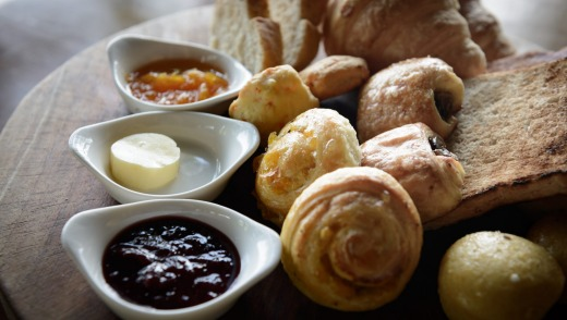 A selection of bread and pastry, accompanied with condiments.