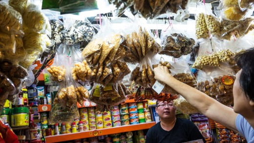 A customer reaches for produce at Singapore's Tiong Bahru Wet Market.
