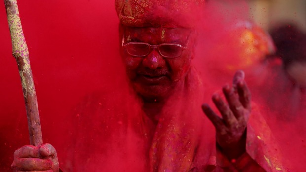 An Indian man smeared with coloured powder takes part in the Holi Festival celebrations in Mathura, India.