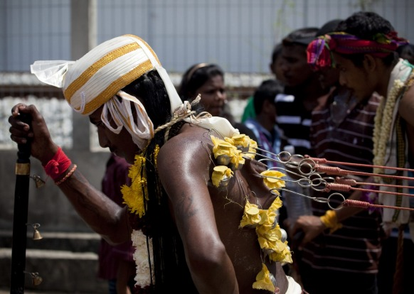 Hooks are used to attach heavy objects to the pilgrims body before the ascent to the caves. Thaipusam Festival, Batu ...