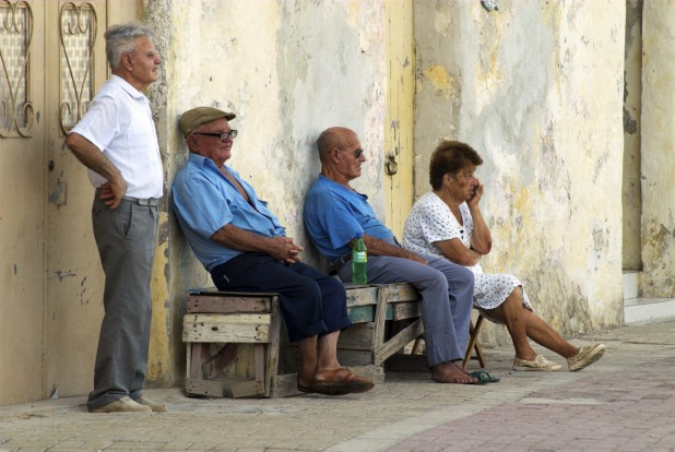 Elderly people having afternoon break on wooden bench, Marsaxlokk.