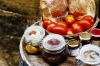 Bread, plum tomatoes, jars and honey on top of barrel, Malta.