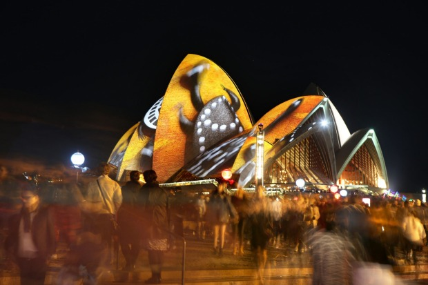 Coloured lights flood Circular Quay and the Opera House during Vivid.