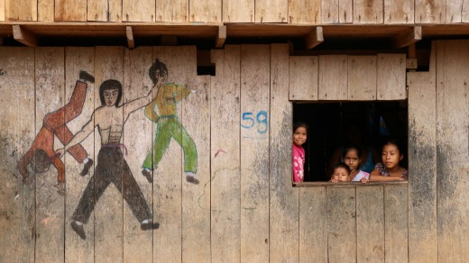 Children at a cut-out window next to kung fu drawings.