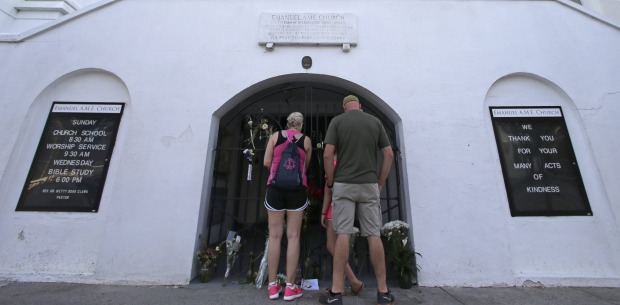 Passersby stop to look at memorials placed in front of Mother Emanuel AME Church in Charleston, US.