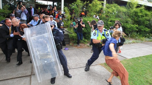 Julia Gillard and Tony Abbott shielded from protesters.