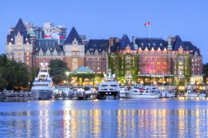 The lights of the grand architecture along the Inner Harbour are reflected in the water.