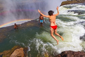 Woman jumps into Devil's Pool at Victoria Falls. It looks like she will be swept over the waterfall but a thick lip of ...