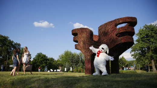 A person dressed as a dog entertains visitors at the Hugs artwork created by Belorussian designers Vasily Timashov and ...