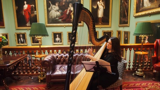 A harpist playing in the reception area of the Garrick Club.