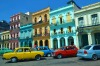 Colourful cars parked in front of historic buildings in Havana, Cuba.