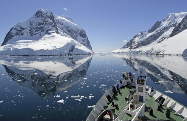 A small cruise ship makes passage through the Lemaire Channel in Antarctica.
