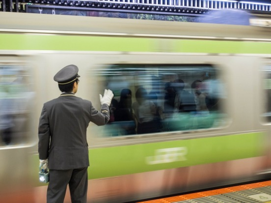 Fast and efficient trains are a way of life in Tokyo. This shot is of a JR train conductor performing his signals as a ...