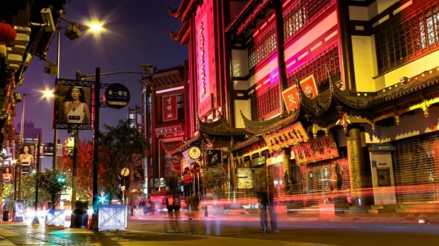 Its the end of a big nights shopping in Shanghai. People wait as traffic goes by outside the colourful Yuyuan markets.