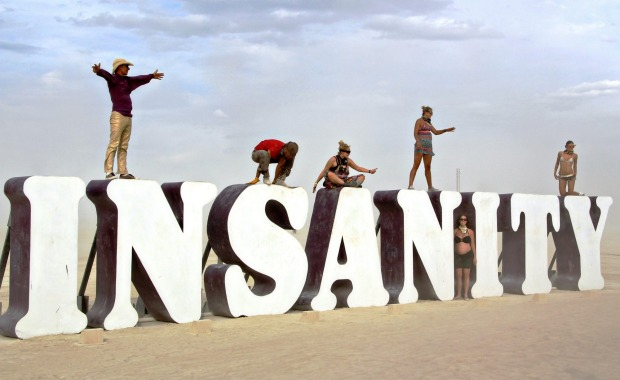 Participants in the annual desert festival Burning Man stand on a art installation.