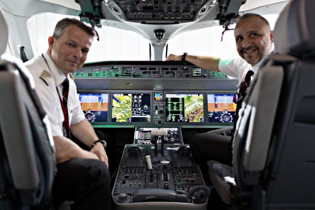Pilots sit in front of electronic flight controls and instruments in the cockpit of a Bombardier CS 100 C Series jet, ...