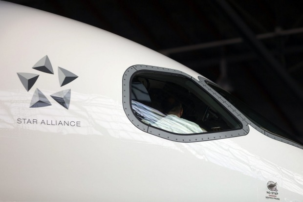 A Star Alliance logo sits outside the cockpit of a Bombardier CS 100 C Series jet, operated by Swiss International Air Lines.