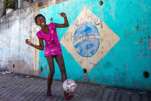 A girl poses while playing football in the Chacara do Ceu favela.