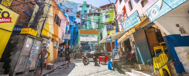 Everyday life in Santa Marta favela, town square named Praca Cantao surrounded by colourful buildings.