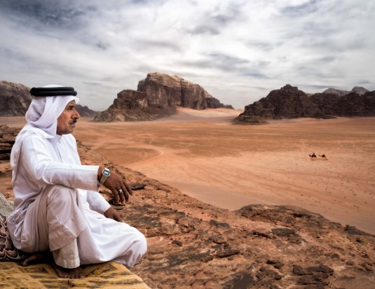 A Bedouin views the panoramic scene from a high vantage point in Wadi Rum Jordan. Wadi Rum is also known as the Valley ...