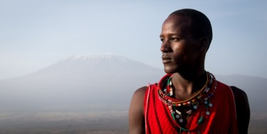 A Maasai warrior stands in his homeland as Africa's tallest mountain, the snow-capped Mt Kilimanjaro, stands in the ...