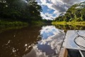 The bow of a touring skiff cruises along the calm waters of the Amazon.