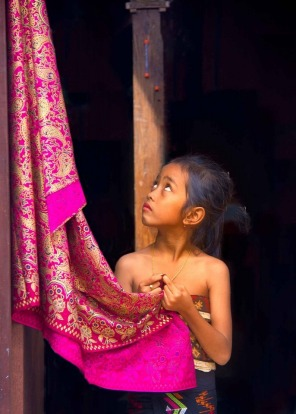 Young girl at the Pandanas Leaf fighting festival in the village of Tenganan, Bali. It's a month long ceremony called ...