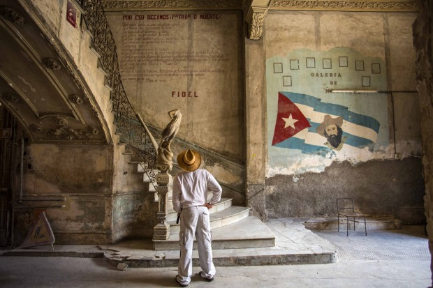 "A tourist looks at quote by Cuban Revolution leader Fidel Castro explaining in Spanish, 'Why we say homeland or death,"" ..."