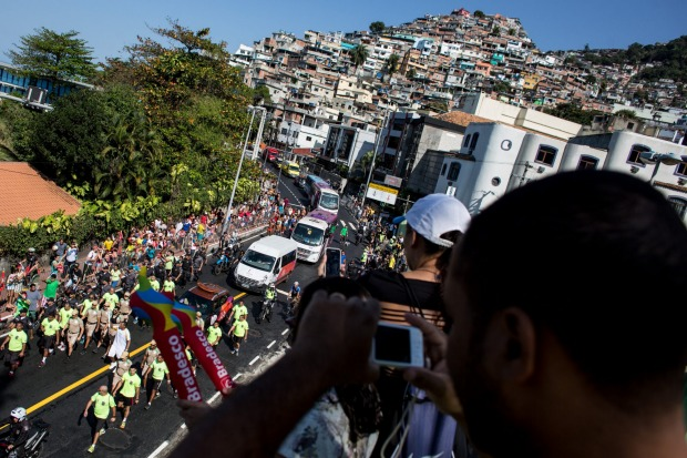 People watch on from the Vidigal favela as the Olympic torch passes by during the Olympic torch relay on August 5.