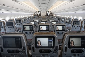 Entertainment monitors sit on the back of passenger seats in the economy class cabin of an Airbus SE A350 aircraft, ...