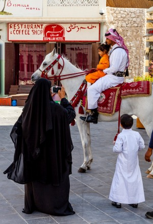 Traditionally clad police atop prancing Arabian horses in Doha's souq.