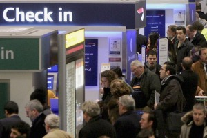 Passengers queue to check-in at Heathrow Airport in London.