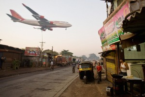 A man makes chapatis as an Air India passenger jet flies over the Jari Mari slum before landing at Mumbai Airport.