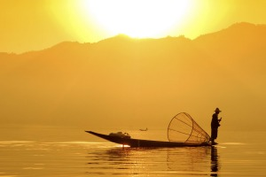 A fisherman plys his trade on Inle Lake at sunset.