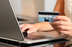 Woman making an online booking with a credit card and a laptop.