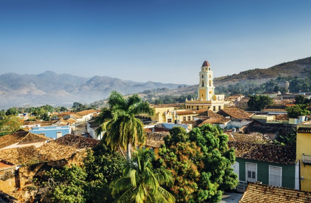 The city of Trinidad, Cuba with mountains in the background and a blue sky. The bell tower belongs to the Iglesia y ...