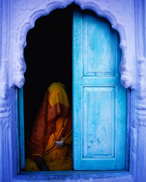Woman sitting near blue door in Jodhpur, India.