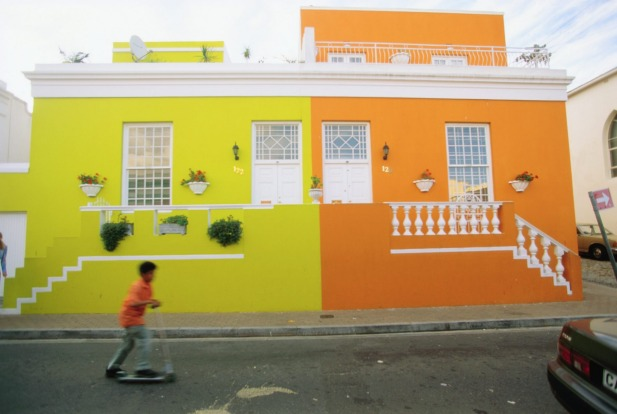 Boys scoots past colourful condominiums in Bo-Kaap area of Cape Town.